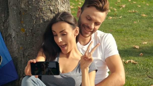 Pár venku. O pořízení Selfie, ukazující znamení míru a baví. Slowmotion.