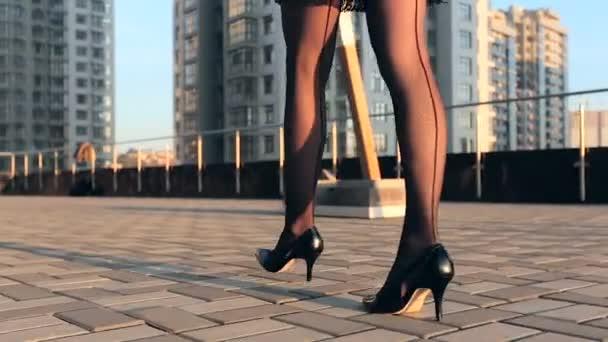 Žena nohy v punčocháče a černé podpatky chůzi na ulici