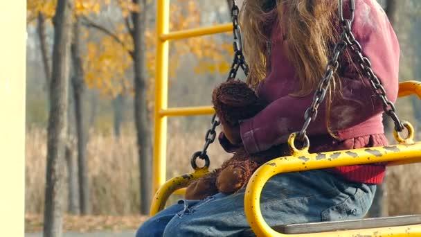 Hajléktalan lány mackó a játszótéren.