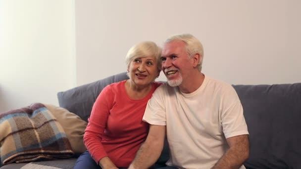 Régi éves feleség és a férj ül a kanapén, és tv-nézés.