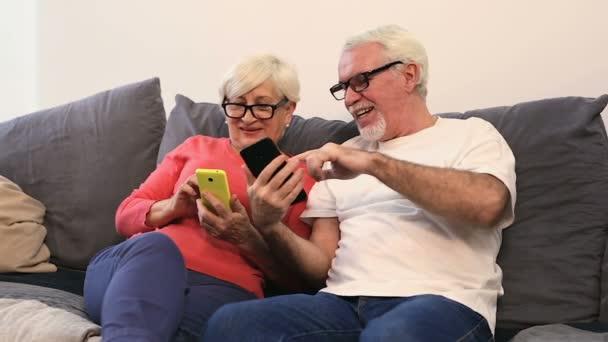 Régi idős házaspár ül a kanapén, gazdaság okostelefonok és megmutatják minden más.