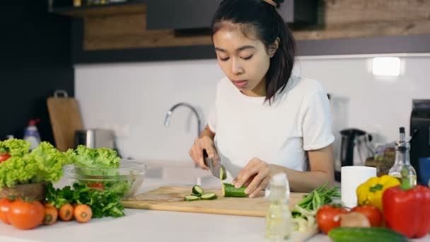 Asijské žena řezání okurek a připravuje salát jídlo v kuchyni.