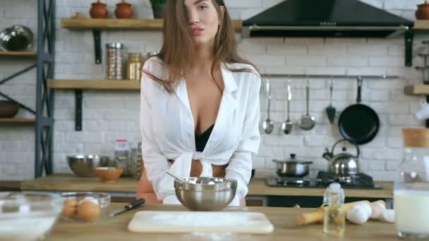 Mladá žena pózní a dívá se na kameru. Doma, kuchyně.