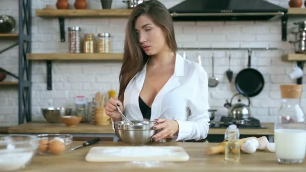 Žena pomalu hnětení vejce v desce. Dívá se stranou. Vaření v kuchyni.