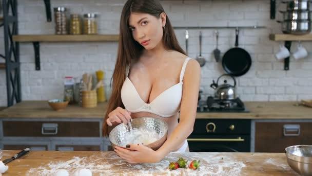 Žena ve spodním prádle připravuje v kuchyni krémový pudin. Testování a pohled na fotoaparát.