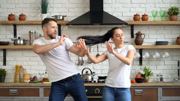 Radostný, šťastný mladý pár tancuje a baví se v kuchyni.