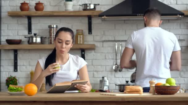 Pár v kuchyni. Snídaně, dopoledne čas. Mladá žena čte knihu a jablko. Chlap jí dát šálek kávy.
