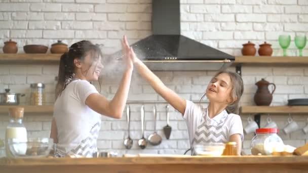 Dvě sestry (nebo matka dcery) se baví, dávají pět. Ruce do mouky, z nichž se dělá oblak mouky.
