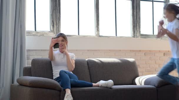 Mladá matka (nebo sestra) sedí na pohovce a bere selfie na smartphone. Její dceruška žertovala a skákala na gauči.