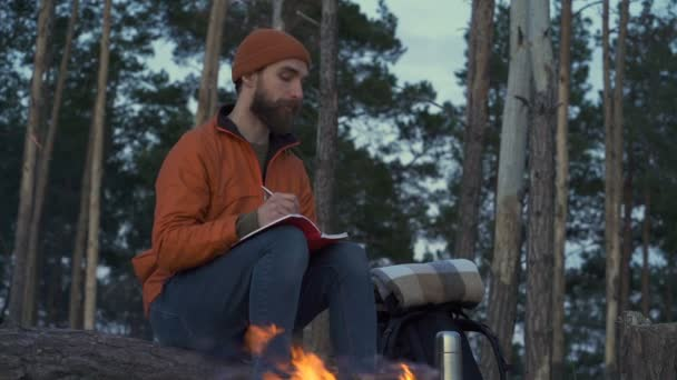 Happy man sitting near the bonfire and writing in the diary.