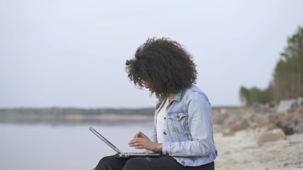 Curly hair afro american woman sitting near the sea with laptop. See good news and showing positive, happy, good news emotion.