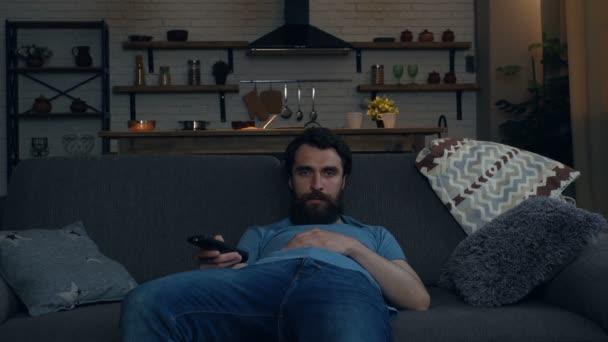 Unavený vousatý muž po práci vypadá doma jako televize. Přepínání kanálů, hledání televizního programu.