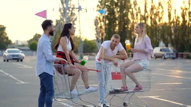 Dva mladí manželé stojí na parkovišti u auta s vozíky pro supermarkety. Usmívají se, mluví a tráví čas pohromadě.