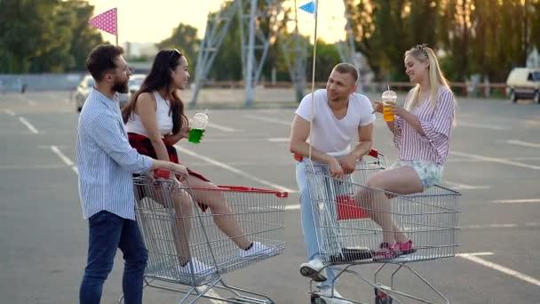 Skupina šťastných přátel, kteří stojí na parkovišti u vozíků pro supermarkety. Chlapi stojí, děvčata sedí na vozících. Usmívají se a mluví.