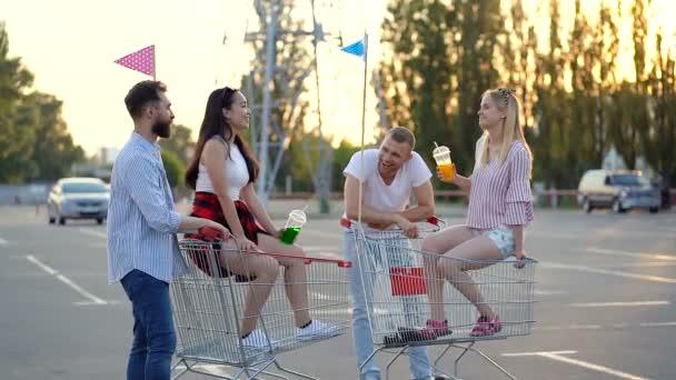 Čtyři přátelé si povídají o parkování v supermarketu. Děvčata sedí v vozících a drží plastikové poháry. Vzepjatý.
