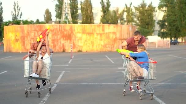 Dvě dvojice přátel, kteří utímají s vozy supermarketů a hrají v boji s vodní pistolí. Vzepjatý. Ruční snímek.