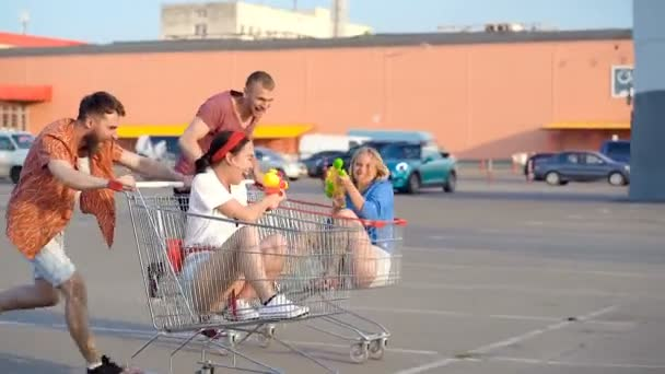 Mladí přátelé běží s vozíky v supermarketu na pekařství a hraje vodní pistole boj. Ruční snímek.