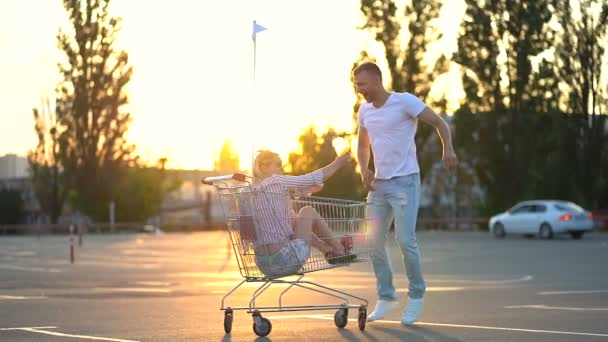 Young couple of caucasian man and blonde woman having fun. Whirling around themselves with supermarket cart. Laughing, screaming. Positive emotions. Slowmotion.