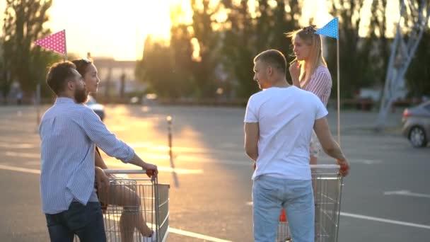 Skupina čtyř přátel s supermarkety, kteří stojí na parkovišti. Mluvili jsme spolu. Blonďák, co se dívá na kameru. Vzepjatý. Pohled zezadu.