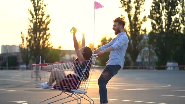 Pár vousatý běloch a asijská žena se baví při parkování na parkovišti. Točí se kolem sebe, směje se a baví si čas. Ruční snímek.