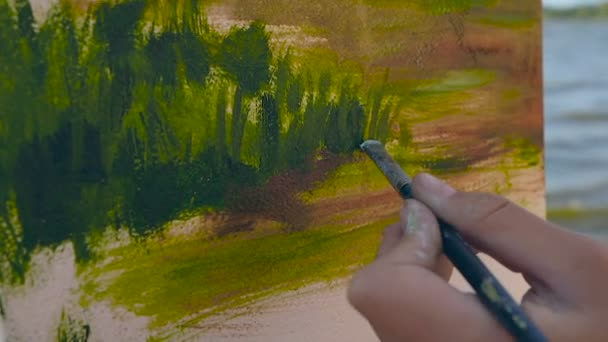 Close up footage of female hand holding brush and painting landscape.