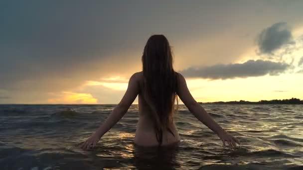 Vonzó fiatal nő ruha nélkül állt a tengerben. Esős időjárás, naplemente idő.