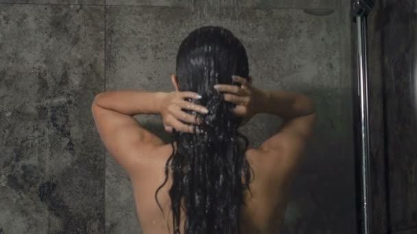 Žena se předvádí v koupelně. Pohled zezadu.