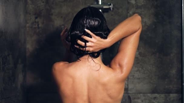 Brunetka se v koupelně a umývání vlasů předvádí. Pohled zezadu.