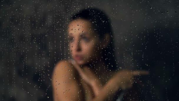 Portrét mladé ženy bez emocí v koupelně. Zaměřit se na kapky skla a vody.