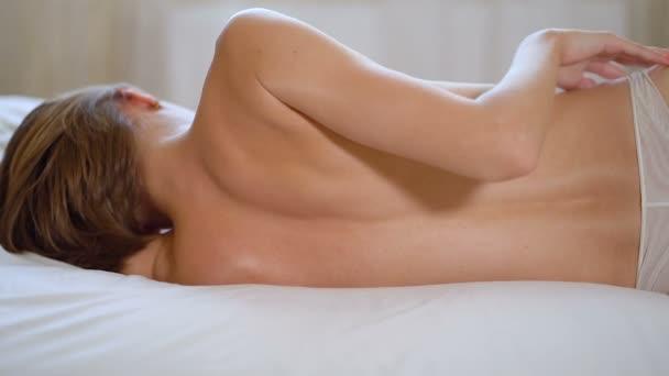 Štíhlá žena ležela v posteli v bílých kalhotách. Pohled zezadu, ruční snímek.