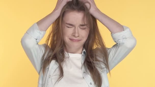 Close-up portrait of stressed, unhappy young woman. Slowmotion. Yellow background.