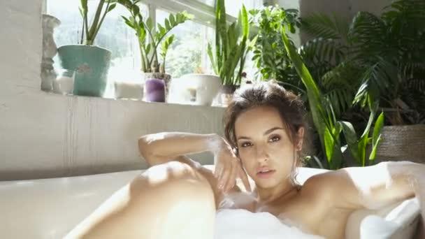 Fiatal nő fekszik a fürdőkádban, és pihentető.