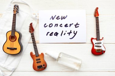 Medical mask, guitars and card with message New Concert Reality on wooden background. Quarantine music concept