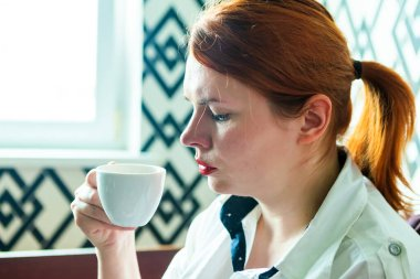 Redhead girl is drinking coffee from white cup