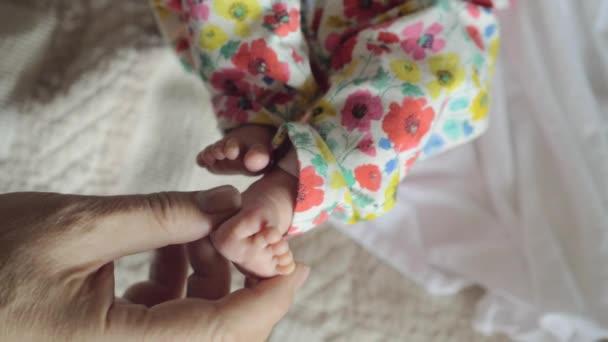Betreuung von Babys. Männliche Hand berührt kleine Füße