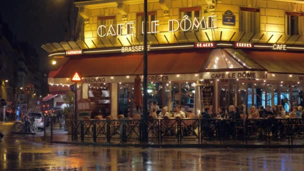 Parisian street with people in cafe, view at rainy night