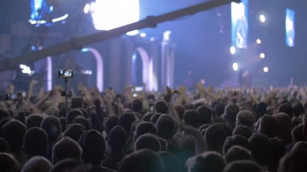Koncertní publikum s rukama nahoru a světlé fázi světla