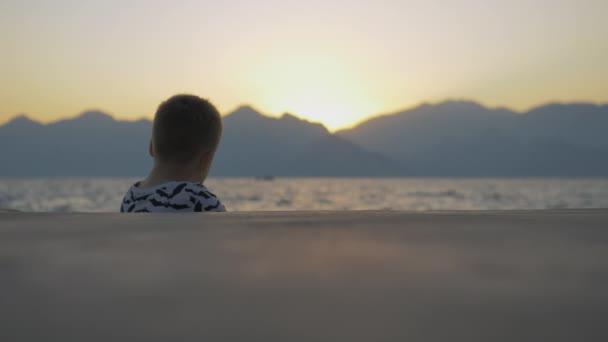 Boy in a shirt with bats sitting near the sea