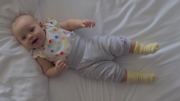 Usmívající se šestiměsíční holčičku ležící na posteli