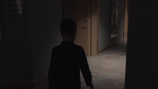 Child walking in hotel hall and opening room door with keycard