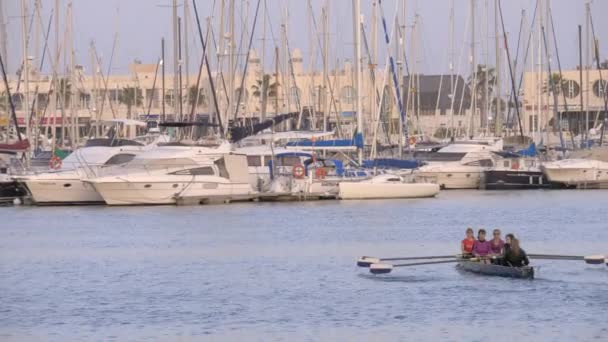 Rowing boat sailing in quay with yachts. Alicante, Spain