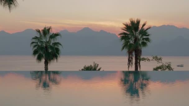 Scény při západu slunce. Bazén s palmami, moře a hory