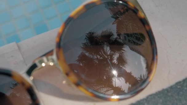 Close-up shot of female sunglasses on swimming pool border with palm and sun reflection. Vacation time
