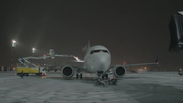 Odmrazování zadního křídla letadla před odletem noc