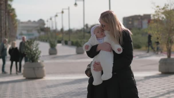 Mother holding her baby girl outside
