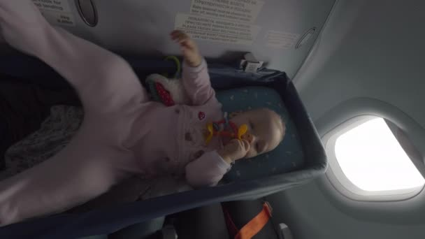Baby girl in airplane bassinet