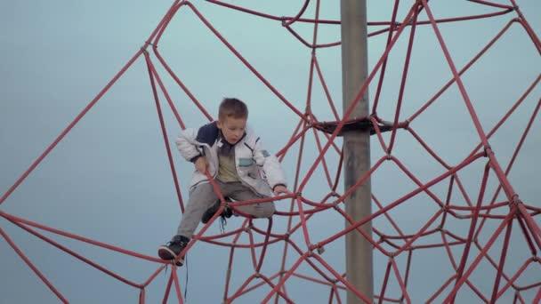 Ein Junge auf einem roten Kletternetz