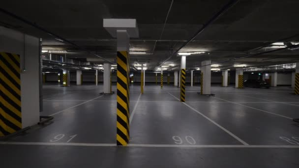 Rotating shot of almost empty underground parking garage with just two cars there