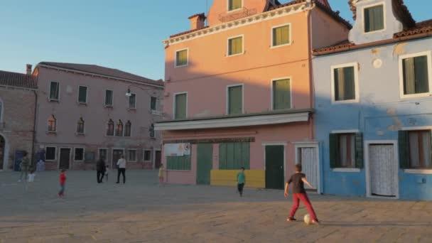 Playful kids at Baldassarre Galuppi Square in Burano, Italy