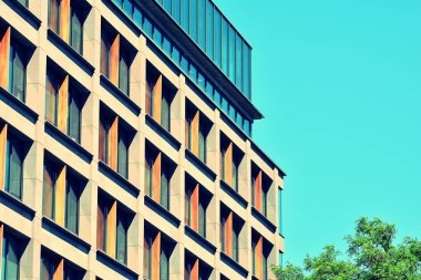 Modern office building on a clear sky background. Retro stylized colorful tonal filter effect